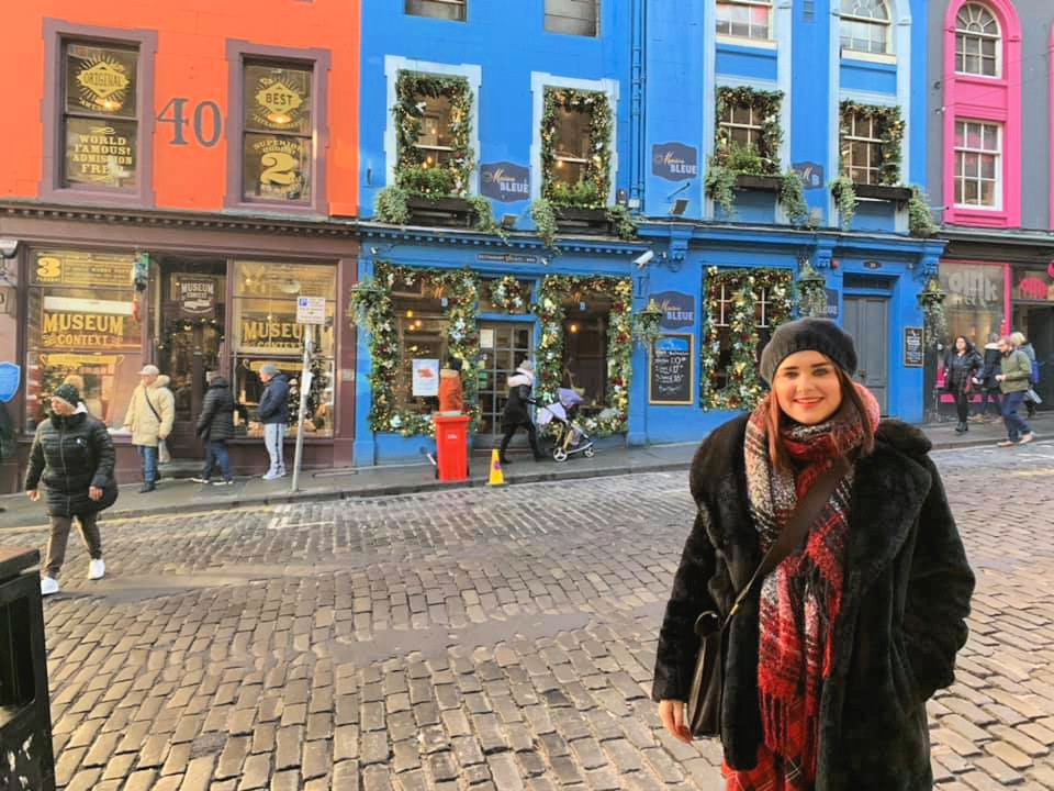 Woman stood in front of colourful buildings on Victoria Street Edinburgh